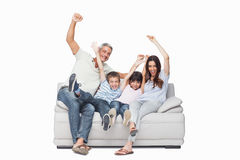 Family sitting on sofa raising their arms Stock Photography