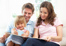 Family Sitting On Sofa Reading Book At Home Royalty Free Stock Image
