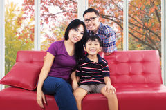 Family sitting on sofa and smiling at camera Royalty Free Stock Image