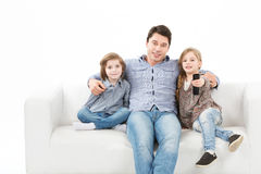 Family sitting on sofa smiling at camera on white background Stock Images