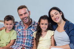Family sitting on sofa and smiling royalty free stock image