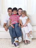 Family sitting on sofa together Royalty Free Stock Photography