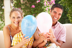Family Sitting On Sofa Together With Balloons Stock Photos