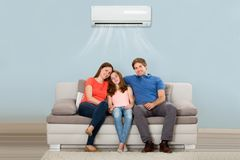 Family Sitting On Sofa Under Air Conditioning. Happy Family Sitting On Sofa Under Air Conditioning At Home stock images
