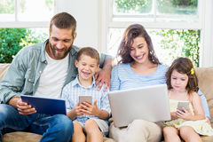 Family sitting on sofa and using a laptop, tablet and phone Royalty Free Stock Photography