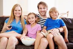 Family Sitting On Sofa Watching TV Together Stock Photography