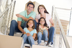 Family sitting on staircase with boxes in new home royalty free stock image