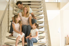 Family sitting on staircase smiling Stock Photo