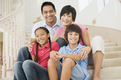 Family sitting on staircase smiling Stock Photography