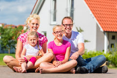 Family sitting on street in front of suburban house Stock Photo