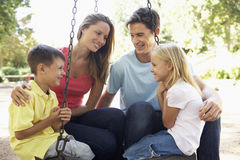 Family Sitting On Swing In Playground Royalty Free Stock Photo