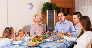 Family sitting at table for dinner Stock Photo