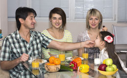 Family Sitting At Table Eating Meal Together Stock Image