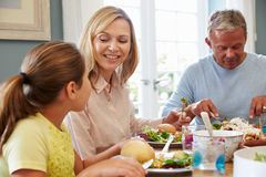 Family Sitting At Table Enjoying Meal At Home Together Royalty Free Stock Photos