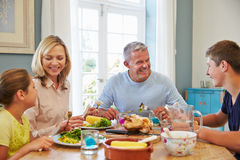 Family Sitting At Table Enjoying Meal At Home Together Stock Photo