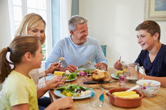 Family Sitting At Table Enjoying Meal At Home Together Royalty Free Stock Images