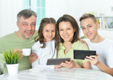 Family sitting at table with gadgets Royalty Free Stock Photography