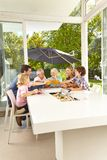 Family is sitting at the table having lunch. Big family is sitting at the table having lunch and toasting with juice royalty free stock photos