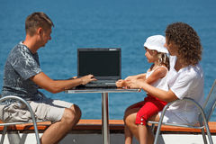 Family sitting at table with laptop stock photo
