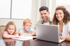 Family sitting at table with laptop and colouring book. At home in kitchen Stock Photography