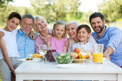 Family sitting at table outdoors, smiling Stock Photography