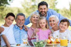 Family sitting at table outdoors, smiling royalty free stock photos