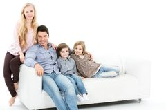 Family sitting together on the couch isolated. Stock Photo