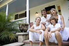 Family sitting together on front porch steps Royalty Free Stock Photo