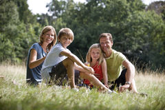 A family sitting together on the grass Stock Photo
