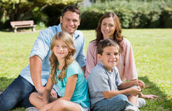 Family sitting together smiling at camera Stock Photos