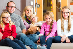 Family sitting together on sofa Stock Photos