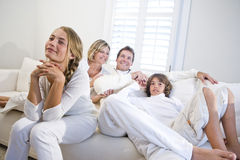 Family sitting together on white sofa watching TV Stock Photos