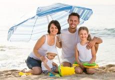 Family sitting under umbrella on the beach Stock Photos