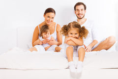 Family sitting on white bed in pajamas together Royalty Free Stock Image