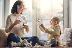 Family sitting by the window. Merry Christmas and happy holidays! Happy loving family sitting by the window and making paper snowflakes for decoration windows Stock Photography