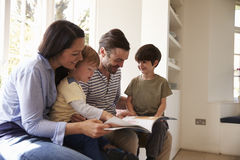 Family Sitting On Window Seat Reading Story At Home Together Stock Photo