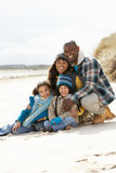 Family Sitting On Winter Beach royalty free stock photography