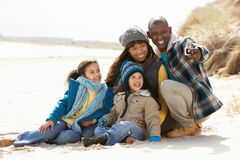 Family Sitting On Winter Beach Stock Photo
