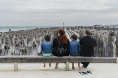 Family sitting on wooden bench in the pier Royalty Free Stock Images