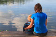 family sitting on wooden dock stock photography