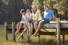 Family Sitting On Wooden Jetty Looking Out Over Lake Royalty Free Stock Images