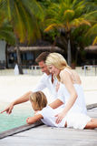 Family Sitting On Wooden Jetty Royalty Free Stock Photo