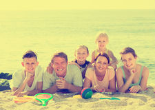 Family of six people lying together on beach Royalty Free Stock Image