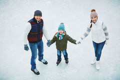 Family in skating rink. Two parents with son skate in ice skating in winter Stock Images