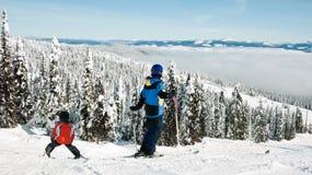 Family ski. Boy learns to ski down slopes with family / mother / teacher Stock Photos