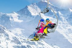 Family in ski lift in mountains. Skiing with kids. Family in ski lift in Swiss Alps mountains. Skiing with young kids. Father, mother and children sitting in ski stock photo
