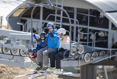 Family on Ski Lift with Young Toddler Going up the Mountain. Stock Photos