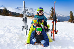 Family in ski masks laying and kid on shoulders Stock Image
