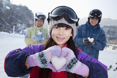 Family in Ski Resort, Daughter Showing Snow Heart Royalty Free Stock Photography