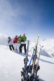 Family of skiers smiling together on mountain top royalty free stock photos